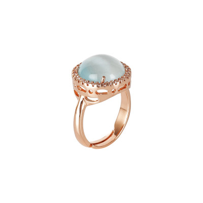 Ring with light blue cabochon flecked crystal and zircons