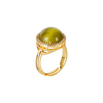 Ring with green olivine cabochon crystal, flecked with zircons